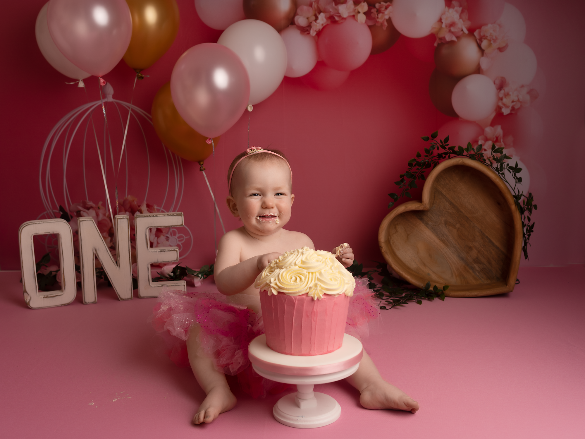 one year old girl with a cake on her cake smash session